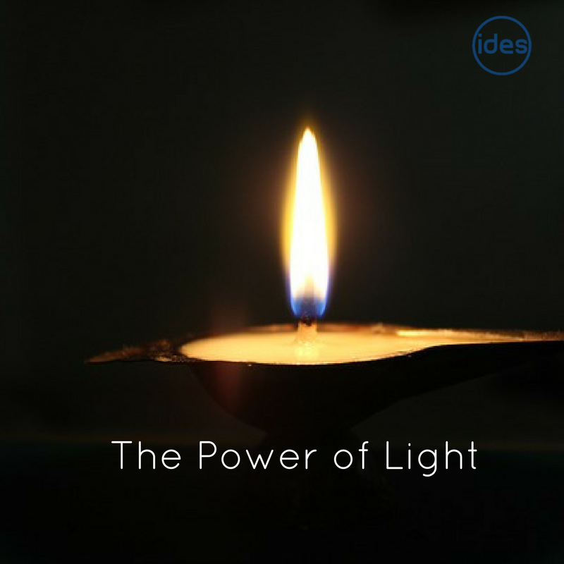 Cly pot with lit candle and 'the Power of Light' written over the top.